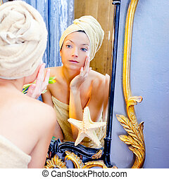 Beauty woman with towel looking at golden mirror