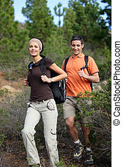 Young couple hiking through the woods