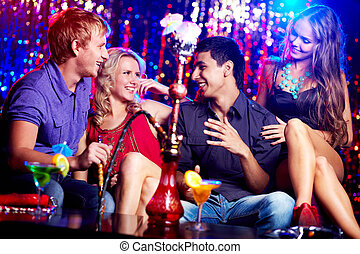 Friends in hookah room - Image of two happy couples...