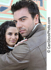 Couple leaning against wall