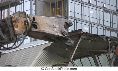 Demolition. - Hydraulic arm with claw, demolishing a city...