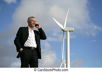 Man on mobile phone next to wind turbine