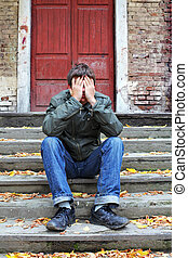 sad young man with hidden face on the old house background
