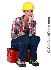 A female worker sitting on her toolbox.