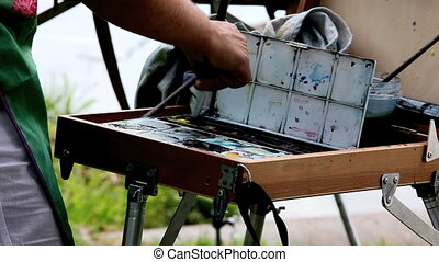 Easel - artist paints watercolors