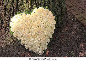 Heart shaped sympathy flower arrangement with white roses...