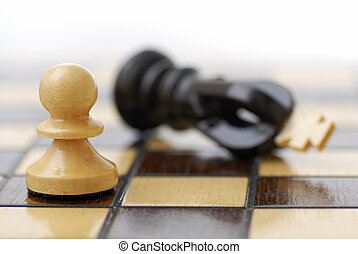 White Pawn Standing Over Defeated King. - White Pawn...