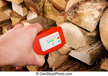 Wood moisture meter - Hand with a wood moisture meter in...