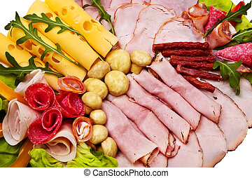 Dish with sliced smoked ham, salami rolls and cheese over...