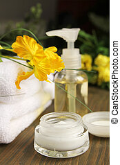 Beauty items - Cream, beauty items and towels on a wooden...