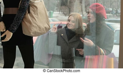 Window shopping - Two girls with shopping bags looking at...