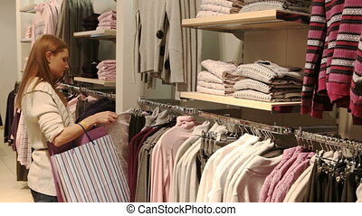 Picking clothes - Pretty blond girl choosing a blouse and a...