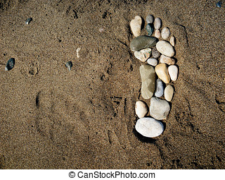 Stone foot in the sand - Single footprint made of stones in...