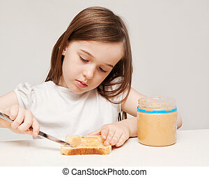 A young girl spreads peanut butter onto a piece of wholemeal...