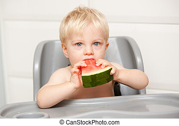 This photo is of a adorable little one year old boy eating watermelon in his high chair at home.  He is definitely enjoying himself.