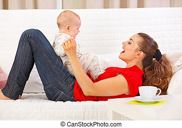 Smiling mother and cute baby playing on divan