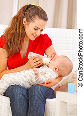 Happy mother sitting on sofa and feeding baby