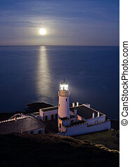 Lighthouse with Full Moon Reflecting in Sea - Lighthouse...