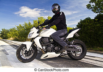man with a motorcycle - View of a man with a motorcycle on a...