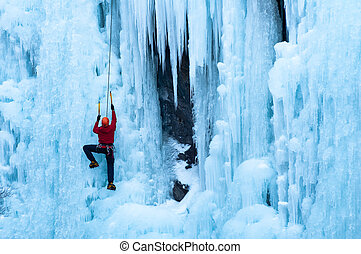 man in red coat climbing ice - Athletic man in red coat with...
