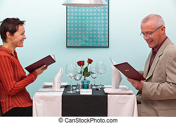 Mature couple in a restaurant reading menus - Photo of a...
