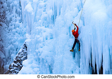 athletic male in red coat climbing ice in the Uncomphagre...