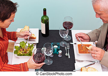 Mature couple eating in a restaurant overhead shot - Photo...