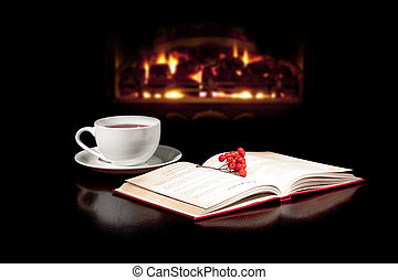 Cup of peace - Cup of tea and book on the table Fireplace in...