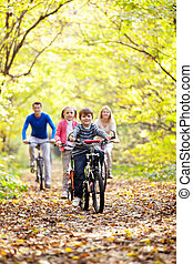 Outdoors - A young family with children on bicycles
