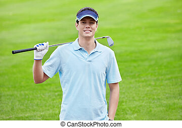Golfer - A young man with a stick on the golf course