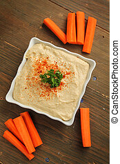 Hummus with carrots - Top view of a hummus in a white...