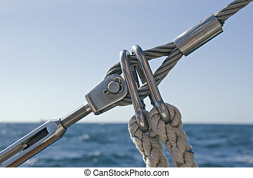 Detail of sailboat rigging against water and sky