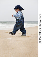 young child walking on a beach - View of a happy young child...