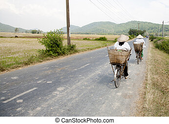 Vietnam rural street - Two cyclists on a rural street in the...