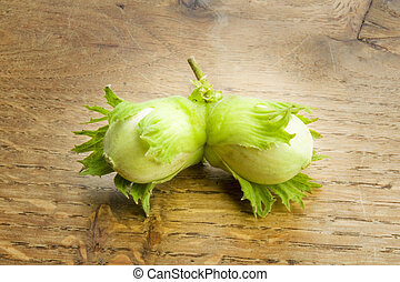 Pair of unripe hazelnuts on wooden background