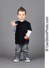 Little boy waving - Cute and hip little boy wearing jeans...