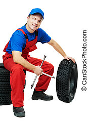 automobile mechanic with car tire and spanner - serviceman...