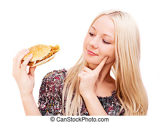 woman eating a hamburger - thoughtful young woman eating a...