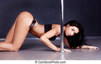 pole dancer - Young sexy pole dance woman against dark...