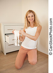 Pregnant woman with babys tights - Young pregnant blonde...