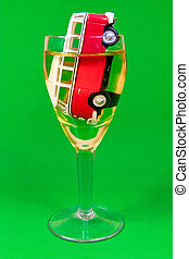 drunk driving concept car in a glass on green background