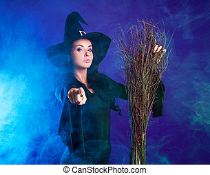 beautiful witch - young brunette witch with a broom pointing...