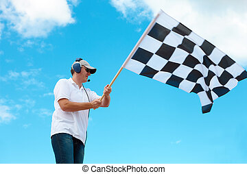 Man waving a checkered flag on a raceway - Man with headset...