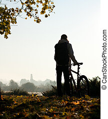 Silhouette of woman with bicycle by the break of day -...
