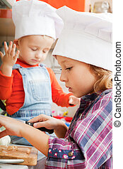 girl in a cook cap helps to make a dinner.