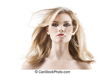 classic beauty portrait of young sexy girl with hairstyle and flying hair from wind, she is in front the camera looks in to the lens with searious expression