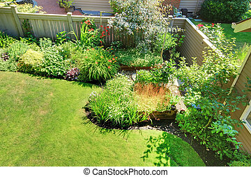 Fenced back yard corner with flowers and shrubs landscape. -...