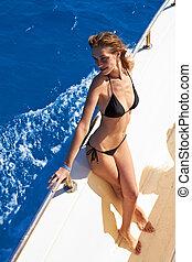 Young woman in bikini posing on yacht - Young woman in...