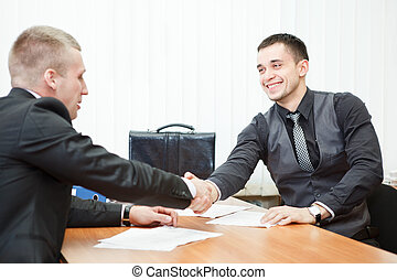Young business man shaking hands with colleague across the...