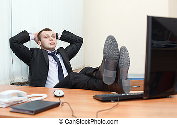 Handsome young business man resting with feet on desk